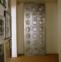 An antique metal door punctured with a series of porthole windows is displayed propped against one wall of a corridor next to a collection of framed paintings and prints