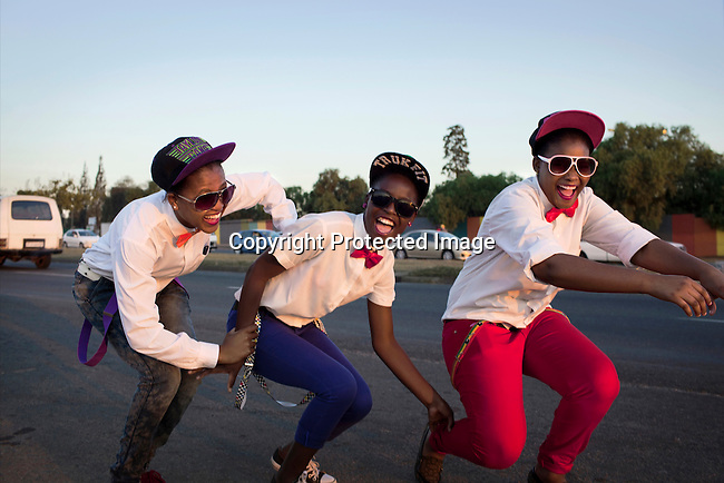 SOWETO, SOUTH AFRICA APRIL 27: Girls part of group that call themselves the three musketeers walk around Soweto dancing and singing on the streets on April 27, 2013 in Bara section Soweto, South Africa. They are dreaming of being discovered. Soweto today is a mix of old housing and newly constructed townhouses. A new hungry black middle-class is growing steadily. Many residents work in Johannesburg but the last years many shopping malls have been built, and people are starting to spend their money in Soweto. (Photo by: Per-Anders Pettersson)
