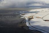 Winterse luchtfoto ZW-Ameland met Waddenzee en sneeuwbui op achtergrond.