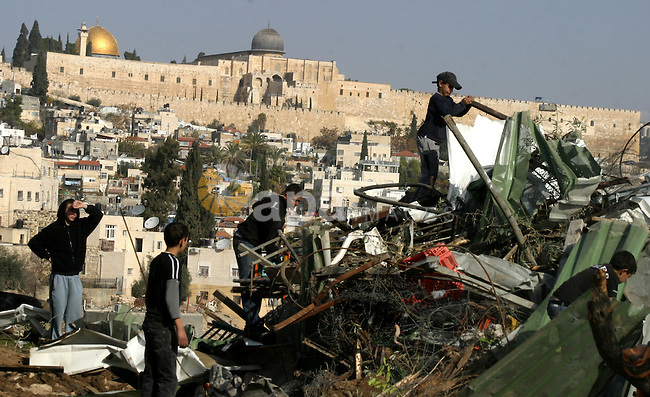 Palestinians sit on the rubble of a storehouse after an Israeli bulldozer destroys a storehouse in east Jerusalem neighborhood of Silwan on Dec 20,2011, where Palestinian houses are threatened to be demolished by the Israeli city's municipality. Photo by Mahfouz Abu Turk