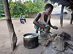 "Joyce Dzongololo prepares to cook porridge made from sorghum for breakfast in Chidyamanga, a village in southern Malawi that has been hard hit by drought in recent years, leading to chronic food insecurity, especially during the ""hunger season,"" when farmers are waiting for the harvest."