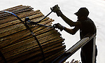 "Ronnie ""Bin Laden"" Jones, 53, cuts the ties on a pack of ""sticks,"" small pieces of scrap wood used to separate layers of green wood so it dries properly in the open air, then in a special lumber kiln."