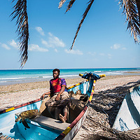 Dec. 30, 2014 - Socotra, Yemen. A fisherman with a turtle he caught near Hadibo. Though turtles are protected, they are regularly caught for food. © Nicolas Axelrod / Ruom