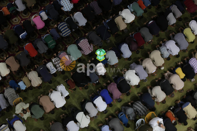 """Palestinian Muslim worshipers perform """"Taraweeh"""", nightly prayer of the month of Ramadan, at Sayed Hashim mosque, in Gaza city, on May 26, 2017. Photo by Mohammed Asad"""
