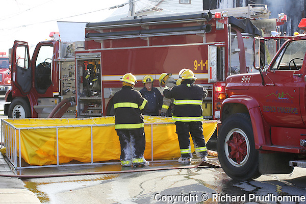 Firemen filling portable water tank at the scene of a fire