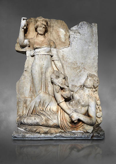 Roman Sebasteion relief  sculpture of the goddess Roma and Ge (Earth),  Aphrodisias Museum, Aphrodisias, Turkey.  Against a grey background. <br /> <br /> The goddess Roma holds a spear and wears a crown in the form of a city wall. Earth reclines half naked leaning on a pile of fruit. She holds a cornucopia full of more fruit. A baby child (now damaged) climbs up the horn she holds. The relief represents Earths fertility and abundance overseen by Rome.