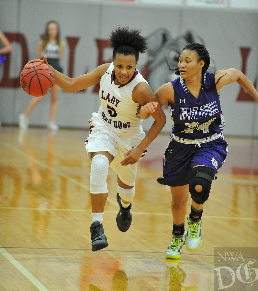 NWA Democrat-Gazette/MICHAEL WOODS &bull; @NWAMICHAELW<br /> Springdale's Kierra Lang (5) tries to drive past Fayetteville defender DaShundra Morgan (24) Friday, January 15, 2016 during their game at Springdale High School.