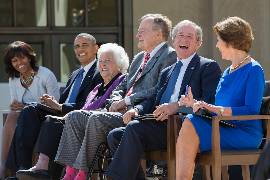 Former President George W Bush laughs with his father George H.W. Bush at the dedication of the George W. Bush presidential library on the campus of Southern Methodist University in Dallas.    On the left are first lady Michelle Obama,  President Obama,  former first lady Barbara Bush.   On the right is former first lady Laura Bush.