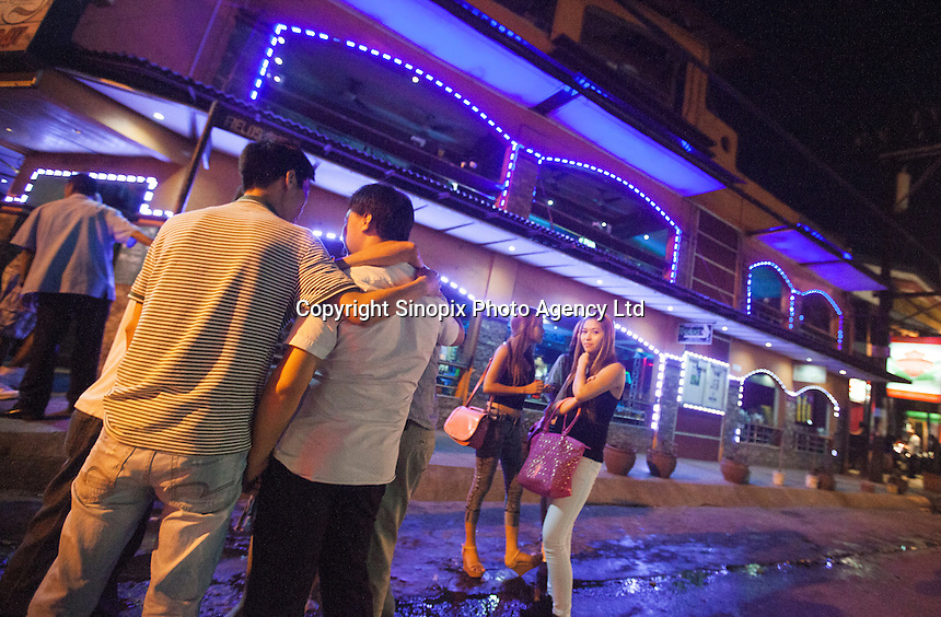 Men consider their options in front a girly bar on Fields Avenue, the main strip of bars offering cheap prostitutes that runs through Angeles City, Republic of the Philippines, 08 November 2014. The 'sin city', which sprung up on the fringes of a US Air Force base during the Vietnam war, has a reputation for cheap sex, and was a favourite destination for alleged murderer Rurik Jutting, who used to fly to Angeles City from Hong Kong for debauched weekends. The British banker is currently on remand at a secure facility in Hong Kong for allegedly murdering two Indonesian prostitutes in his flat whilst high on alcohol and cocaine.