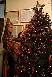 A Palestinian woman wearing traditional clothes decorates a Christmas tree inside the municipality building in the West Bank city of Bethlehem on December 15, 2009. Christians Pilgrims and tourists are expected to visit Bethlehem, the alleged birthplace of Jesus Christ, this coming Christmas. According to the Christmas story, the three Kings who visited Jesus Christ in Bethlehem followed a star until they found him in a manger in this now holy town.Photo by Najeh Hashlamoun
