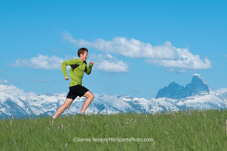 Trail runner Evan Honeyfield runs through a meadow in the Big Hole Range of Idaho as the snow-covered Teton Range loom across the valley in Wyoming.