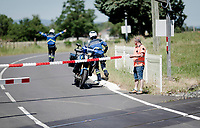 as the peloton approaches the lights (and sirens) at a railroad crossing start to go off and thus the policemen jump on the road to warn the riders + a railroad official extends an extra safety cord to prevent  them from going through<br /> <br />  Stage 5: Boën-sur-Lignon to Voiron (201km)<br /> 71st Critérium du Dauphiné 2019 (2.UWT)<br /> <br /> ©kramon