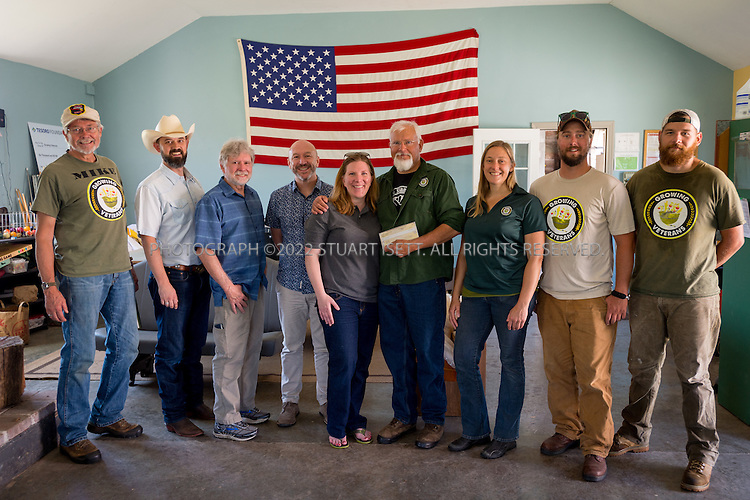 8/12/2016-- Mount Vernon, WA, USA<br /> <br /> Staff from the Schultz Family Foundation visit the Growing Veterans farm in Mt. Vernon, Washington, about an hour north of Seattle.<br /> <br /> <br /> Here, Liz  Willett of the Schultz Family Foundation presents a check to Kenny Holzemer of Growing Veterans.<br /> <br /> Left to right: Mike Hackett, John  McCary (cowboy hat), Bill Smith, Jason Raindrop, Liz  Willett, Kenny Holzemer, Chris Wolf, Joel Swenson, Justin Blotsky.<br /> <br /> <br /> From http://growingveterans.org:<br /> <br /> &ldquo;Since 2012, Growing Veterans has been combining veteran reintegration with sustainable agriculture. Our unique model addresses the growing desire for alternative therapies for Post-Traumatic Stress (PTS) and Traumatic Brain Injury (TBI), as well as suicide prevention through peer-support and Applied Suicide Intervention Skills Training (ASIST) certification. We encourage continued service through volunteerism, and collective impact through collaboration with other local, regional, and national stakeholders.&nbsp; We provide opportunities for vets in transition to develop their resumes and identify how to translate skills learned in the military to new roles in the civilian sector. Further, our vets serve as leaders in the important movement toward sustainable agriculture&rdquo;<br /> <br /> Photograph by Stuart Isett. &copy;2016 Stuart Isett. All rights reserved.