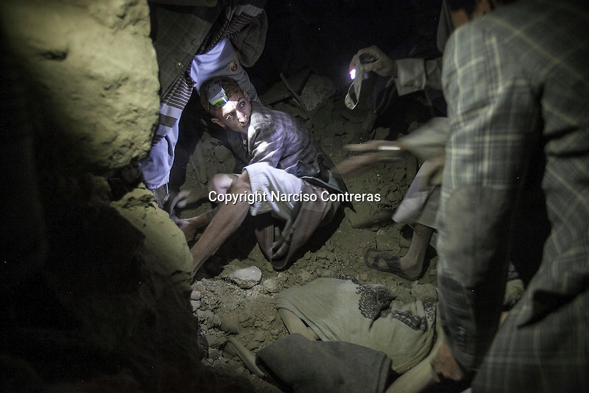 July 15, 2015 - Sa'dah, Yemen: Houthi militants and civilians look for survivors under the rubble of a house building after it was hit by a fighter jet from the Saudi-led coalition in the northern city of Sa'dah, the stronghold of the Houthi movement in Yemen. One family was buried under the rubble during the attack. Two members: the mother and one son (not pictured) died from their injuries, while another son and one daughter (not pictured) survived. (Photo/Narciso Contreras)