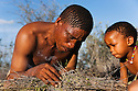 Botswana, Kalahari, bushmen (san) making fire the traditional way by rapidly turning wooden stick