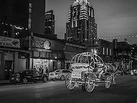 This is Austin cityscape on east sixth street at night in downtown in black and white.  You can see the Frost building and the horse and buggy with tourist  and people waiting to get a pizza at one of the outside window along this popular spot in the city.