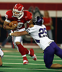 University of South Dakota's Noah Shepard tries to shake the tackle of Winona State's Brent Yule as he scrambles for a first down in the first quarter Saturday night at the DakotaDome in Vermillion. (photo by Dave Eggen/Inertia)