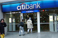 People pass the Citibank in  Shinjuku district of Tokyo. Japan's banking system faces a crunch period in the months ahead due to the shrinking economy and biting recession..