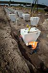 UTRECHT - Op knooppunt Oudenrijn plaatsen medewerkers van Heijmans Infrastructuur betonkoppen op de onlangs geslagen heipalen als onderdeel van een nieuw, experimenteeel wegdek, ModieSlab. Het door Heijmans Infrastructuur, Betonson en ingenieursbureau Arcadis ontwikkelde wegdek bestaat uit een prefab-betonplaat met een toplaag van 'zeer open cement beton' die op een fundering van palen wordt gelegd.  Het wegvak wordt als proef aangelegd in opdracht van Rijkswaterstaat's project Wegen naar de Toekomst, en moet aantonen dat snelwegen niet alleen sneller kunnen worden aangelegd maar eveneens geluidsstilller. ANP PHOTO COPYRIGHT TON BORSBOOM