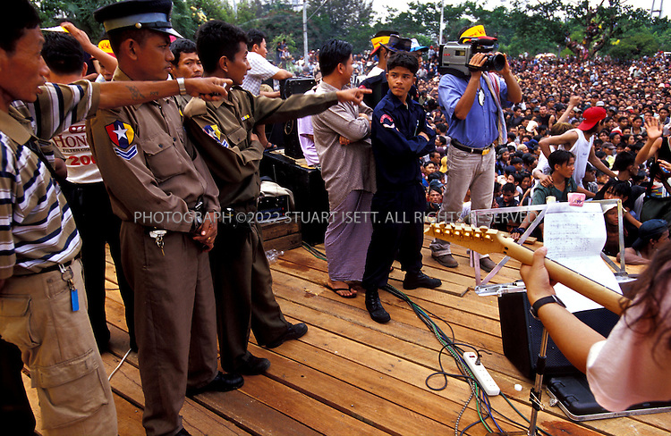 4/13/2002--Rangoon, Burma..Authorities warn fans to calm down while Chit San Muang, Burma's most famous guitarist (right),belts out a tune during an Iron Cross concert...The annual outdoor free concerts are held every April duirng Burma's traditional New Year celebrations. Normally gatherings of young men woiuld be broken up by Burma's ruling junta but the concerts are the one time of year such large gatherings are allowed. Local authorities are nervous that such concerts may turn political or violent and watch the shows carefull for signs of unrest...All photographs ©2003 Stuart Isett.All rights reserved.
