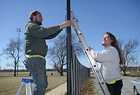 NWA Democrat-Gazette/BEN GOFF @NWABENGOFF<br /> Hunter Horn (left) and Nathan Purcell with Carnahan-White Fence Company in Springdale install new chain-link fabric Thursday, March 3, 2017, around the soccer fields at Memorial Park in Bentonville. The crew was replacing streched out 11.5 gauge fabric with sturdier 8 gauge fabric.