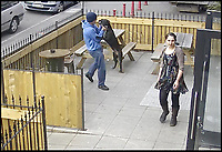 BNPS.co.uk (01202 558833)<br />Pic:   BuffaloBar/BNPS<br /> <br /> The man picks up his dog by the neck after hitting the animal.<br /> <br /> The shocking moment a thug rams his pet dog head-first into a fence and repeatedly punches it has been caught on CCTV.<br /> <br /> The yob owner became angry that the black pitbull-type dog ran off into the front garden of a bar.<br /> <br /> After catching up with the animal, the man grabbed it by the neck and slammed it into the wooden fence.