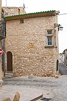 Village street and stone house in the corner. St Jean de Fos village. Languedoc. France. Europe.