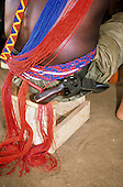 Bacaja village, Amazon, Brazil. Beadwork on a young man's back, with a gun in a holster; Xicrin tribe.
