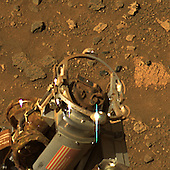 Pasadena, CA - July 21, 2006 -- During recent soil-brushing experiments, the rock abrasion tool on National Aeronautics and Space Administration's (NASA)Mars Exploration Rover (MER) Spirit became covered with dust, as shown here. An abundance of iron oxide minerals in the dust gave the device a reddish-brown veneer. Investigators were using the rock abrasion tool to uncover successive layers of soil in an attempt to reveal near-surface stratigraphy. Afterward, remnant dirt clods were visible on both the bit and the brush of the tool. Designers of the rock abrasion tool at Honeybee Robotics and engineers at the Jet Propulsion Laboratory developed a plan to run the brush on the rock abrasion tool in reverse to dislodge the dirt and return the tool to normal operation. Subsequent communications with the rover revealed that the procedure is working and the rock abrasion tool remains healthy.  Spirit acquired this approximately true-color image with the panoramic camera on the rover's 893rd sol, or Martian day (July 8, 2006). The image combines exposures taken through three of the camera's filters, centered on wavelengths of 750 nanometers, 530 nanometers, and 430 nanometers. <br />  Credit: NASA/JPL-Caltech/Cornell via CNP