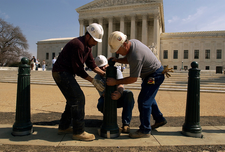 From left, Edwin Medrano, Rich Minnick and Lynn Funk of Walsh Construction, install security bollards in front of the Supreme Court.  The bollards are being installed on three sides of Supreme Court with the fourth side coming in the future.