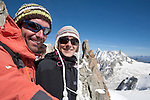 A young French couple wearing hats and sunglasses at Aiguille du Midi, Chamonix-Mont-Blanc in August