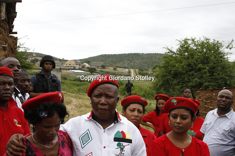 NKANDLA - 11 January 2014 - Economic Freedom Frighters leader Julius Malema speaks to the press at the mud huts of Sthandiwe Hlongwane (around whom he has his arm) where EFF had built a house for Ms Hlongwane. In the background is the residence of President Jacob Zuma.  On the right is EFF's head of international relations and solidarity Magdalene Moonsamy. Picture: Giordano Stolley/Sapa