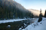 Idaho, North Central, Kooskia, Lowell, Clearwater National Forest. Evening sun lights the mist lingering above the Lochsa River in mid winter.
