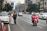 Una giovane coppia di sposi cammina in centro.<br /> A young wedded couple owalking on the street