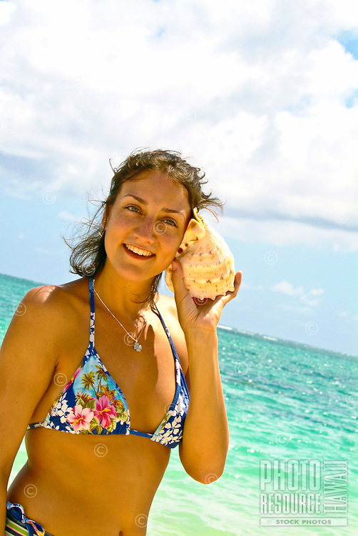A woman wearing a bathing suit listens for the sound of the ocean in a conch shell at Lanikai Beach near Kailua, Windward Oahu.