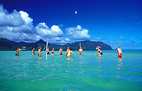 People enjoy playing volleyball in the warm waters of Kaneohe bay on Oahu