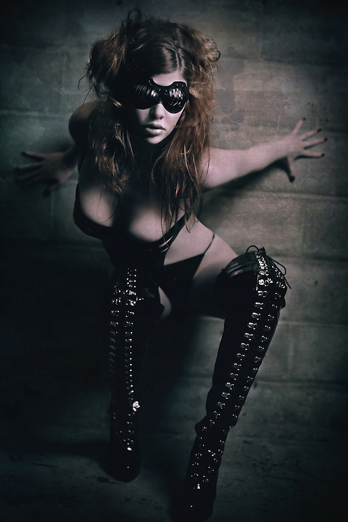 A young woman scantily clad wearing caged goggles posing in thigh-high boots against wall