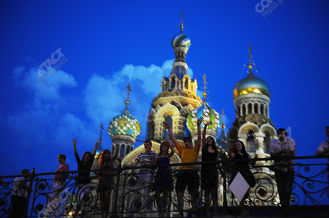 On a bridge over the Griboedev canal, by the Church of the Saviour on Spilled Blood, people waved to passengers of a boat passing underneath. White Nights, St. Petersburg, Russia, July 8, 2010