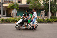 Daytime landscape view of a family riding a motorized scooter on a road in Bozhou in Qiáochéng Qū in Anhui Province.  © LAN
