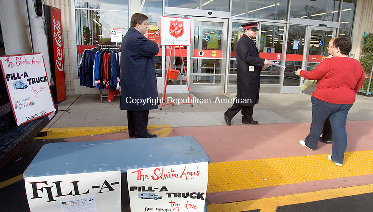 TORRINGTON, CT. 02 November 2011-120211SV05-From left, Philip Hostetler and Mark Devanney hand out flyers while collecting toys for Christmas in Torrington Friday. The Salvation Army was collecting new toys donated for needy families in front of Kmart. The goal was to fill up one of their trucks between 10 a.m. and 3 p.m. They will be filling another truck on December 16th at Walmart in Torrington.<br /> Steven Valenti Republican-American