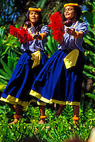 Two beautiful female hula dancers from Halau Mohala Ilima shake their red feather uli uli (gourd) rattles while performing in a lush tropical outdoor setting.