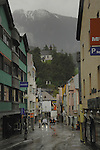 Grey, miserable and raining in the high street looking on to a background of mountain, cloud and a chapel.  Imst district,Tyrol, Austria.