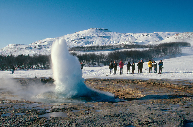 The geysir Strokkur erupting during the winter months with a small audience. Geysir. Iceland.