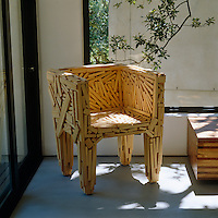 A Fernando and Humberto Campano Favela chair stands in a sunny corner of the bedroom