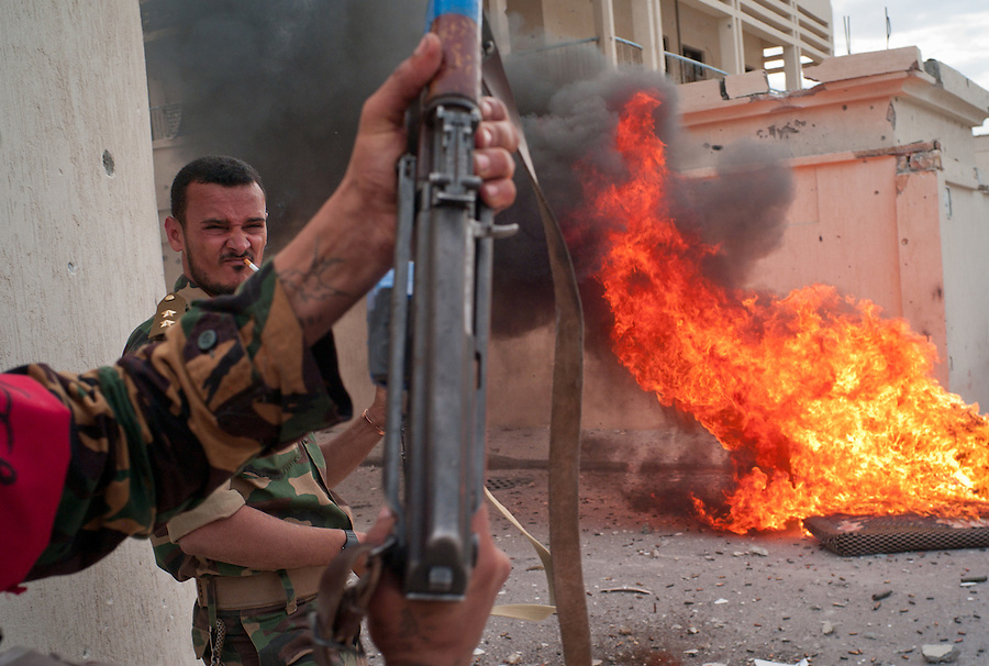 Anti-Gaddafi fighters pause after exchanging fire with Gaddafi loyalists in Sirte, Libya.
