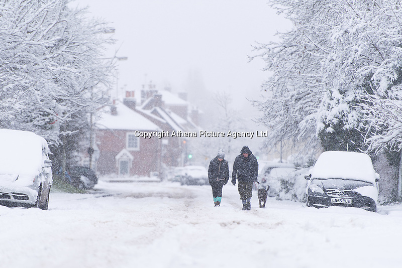 Dog walkers in the snow in the village of Redbourn, Hertfordshire, UK. Sunday 10 December 2017.