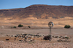 A  wind pump and  water dam for  livestock, Himba. Northern Namibia.