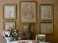 A collection of 18th-century gilt-framed prints is displayed behind a bust of Marie-Antoinette, a 19th century copy of the Houdon original