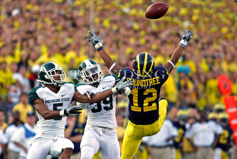 Michigan State cornerback Johnny Adams (5) and safety Trenton Robinson (39) breakup a pass intended for Michigan wide receiver Roy Roundtree (12), in the fourth quarter of an NCAA college football game, Saturday, Oct. 9, 2010, in Ann Arbor. Michigan State won 34-17. (AP Photo/Tony Ding)