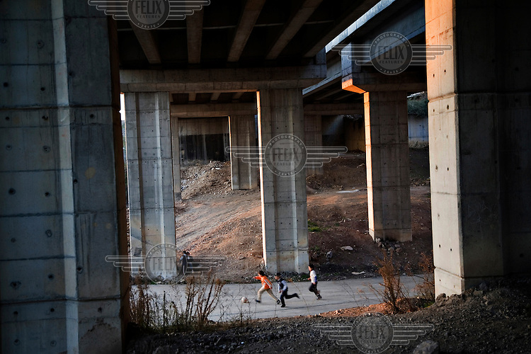 Kids play football under the TEM (Trans European Motorway) in the Cakmak Mahallesi neighbourhood of Istanbul...